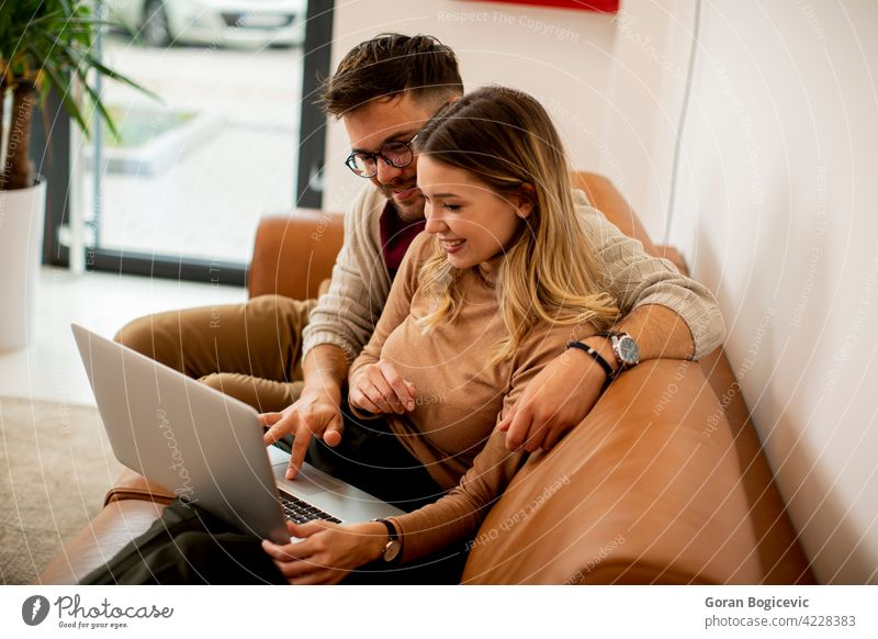 Young couple using laptop together while sitting on sofa at home adult apartment attractive boyfriend carefree caucasian comfortable computer couch day enjoying
