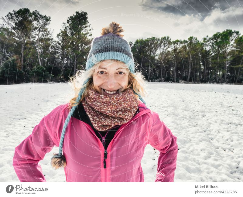 Happy caucasian young woman with a hat and a pink raincoat enjoying snow outdoor in winter time. lifestyle people style of life wanderlust happy having fun