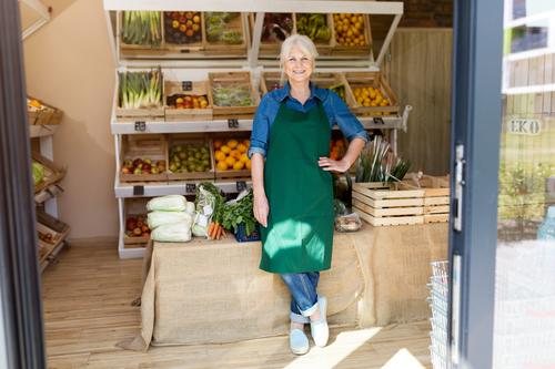 Senior woman working in small grocery store greengrocer groceries people senior mature adult casual attractive female smiling happy Caucasian toothy enjoying