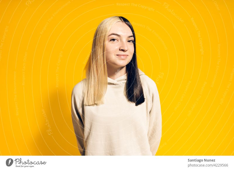 Young Girl Portrait hoodie smile smiling cute innocence cheerful happy happiness studio yellow background portrait looking at camera expression colorful