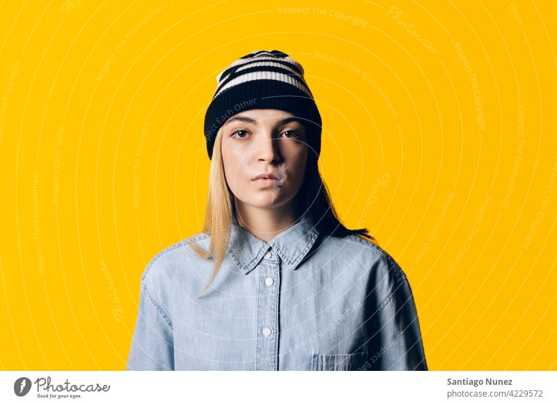 Girl Wearing Hat Portrait studio yellow background portrait looking at camera expression colorful hair style casual young girl female serious two colors hair