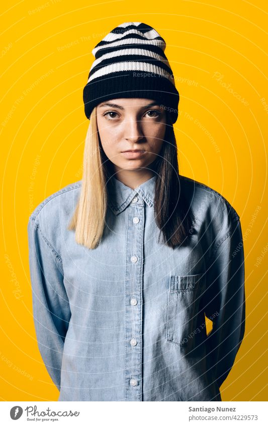 Serious Girl Wearing Hat Portrait studio yellow background portrait looking at camera expression colorful hair style casual young girl female serious