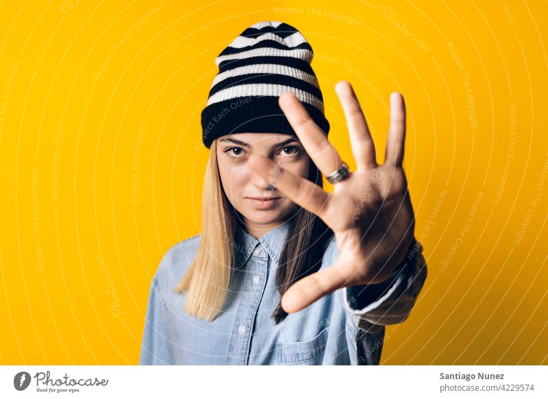 Expressive Young Girl Portrait studio yellow background portrait looking at camera expression colorful hair style casual young girl female serious