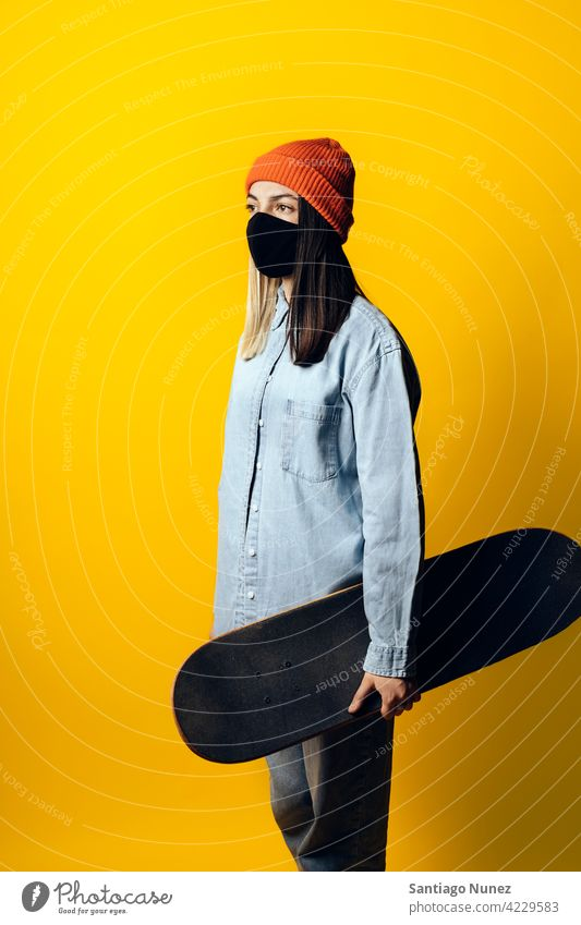 Girl With Skateboard Portrait studio yellow background portrait looking at front expression colorful hair style casual young girl female serious two colors hair