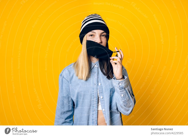 Girl Wearing Face Mask Portrait taking off coronavirus protection new normal new normality cover covering face mask covid19 safety pandemic studio