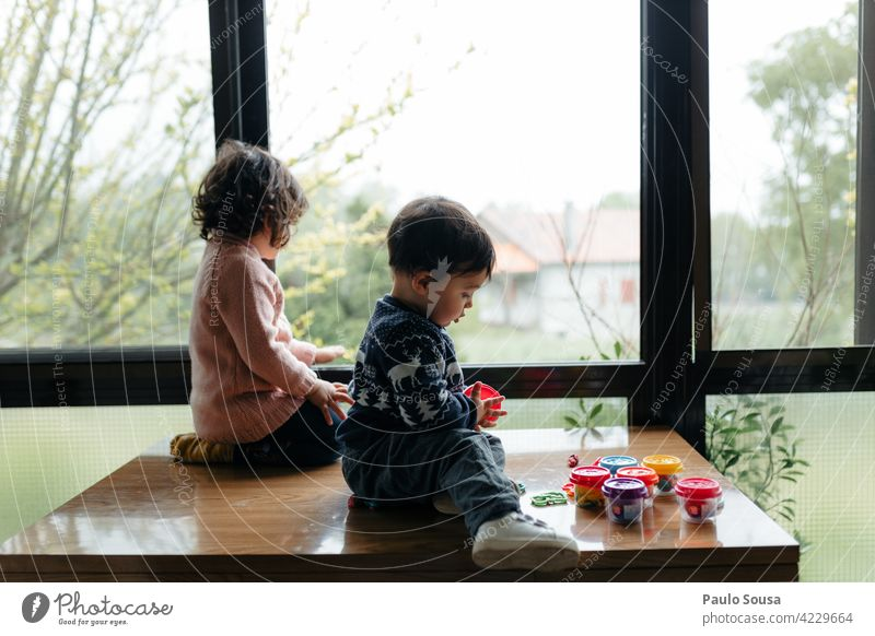Brother and sister at window Brothers and sisters Child 1 - 3 years Caucasian Boy (child) Girl Window rainy Together Infancy Colour photo Human being Toddler