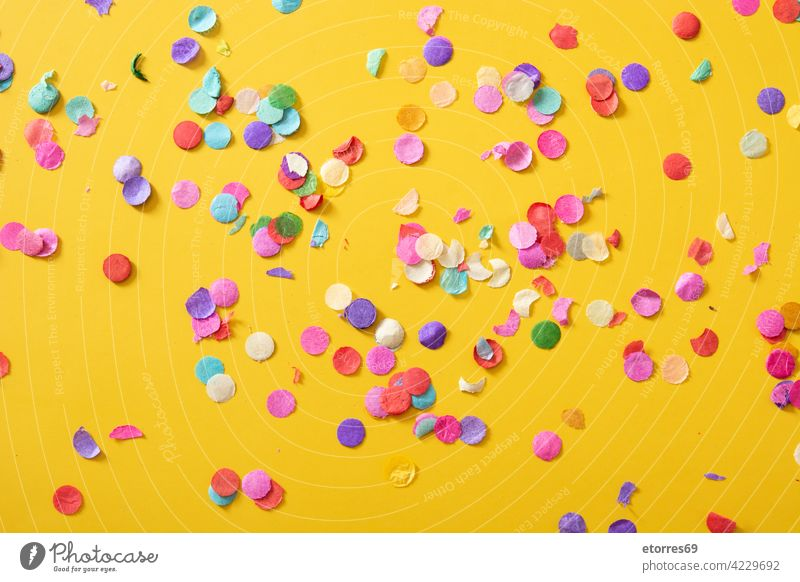 Colorful confetti on yellow background celebration party birthday blue adoration bright circle color colorful concept copyspace decoration decorative greeting