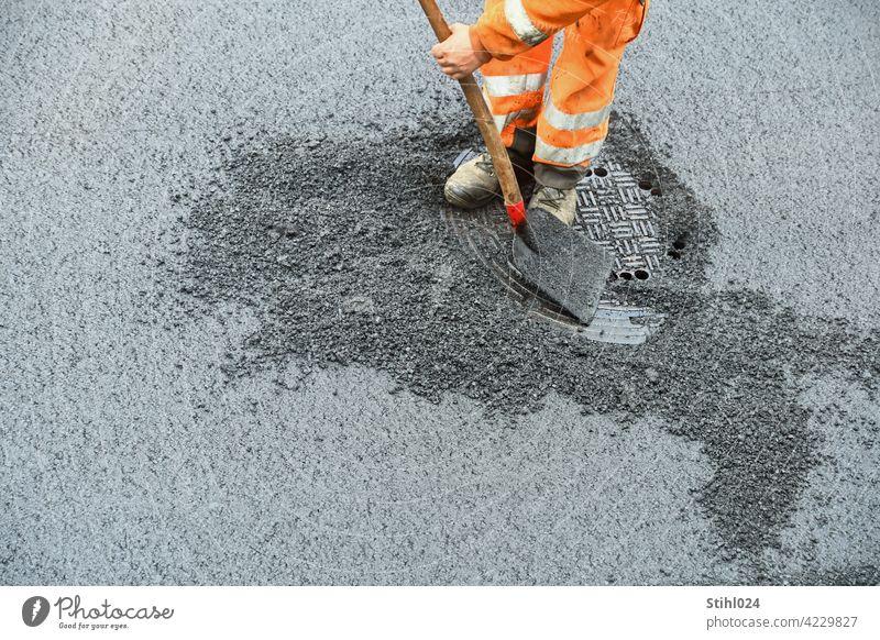 Road construction worker with orange work clothes and shovel roadman Shovel Orange Pants reflective labour Manhole cover asphalt work Asphalt Redevelop repair