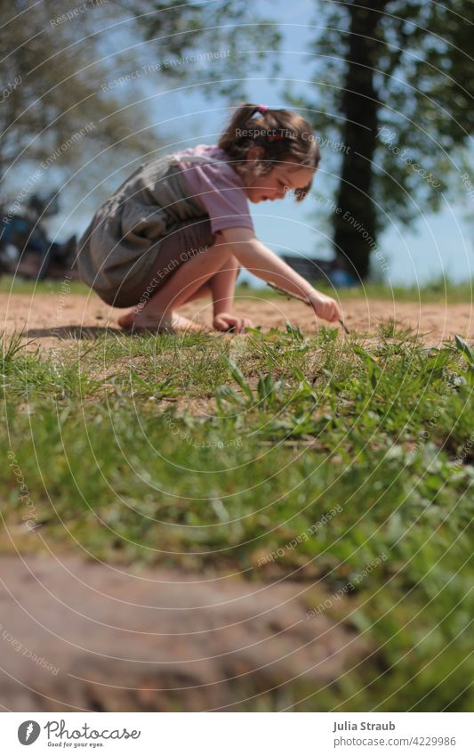 Girl drawing in the sand Playing be out Sand Meadow Grass Barefoot Dress T-shirt Braids Stick Write Draw Painting (action, artwork) Interpret Summer Spring Sun