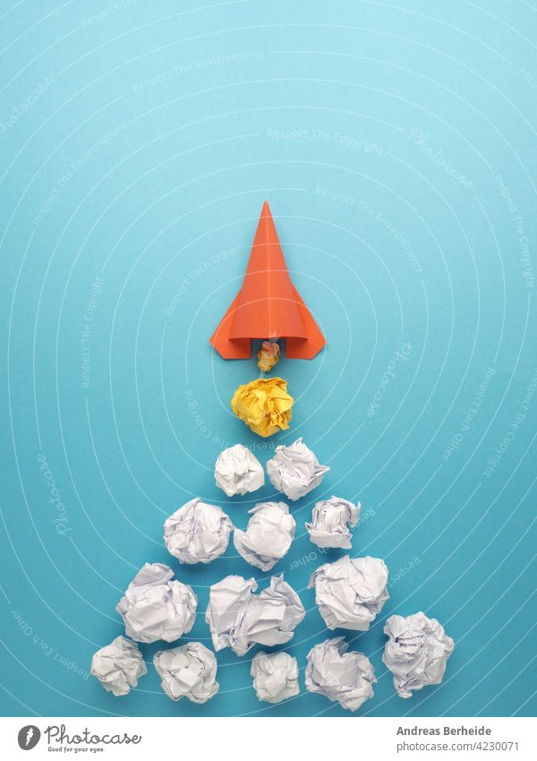 Launching paper rocket with jet stream of paper balls, creativity concept or new ideas metaphor, start up business strategy ambition crumpled paper begin dreams