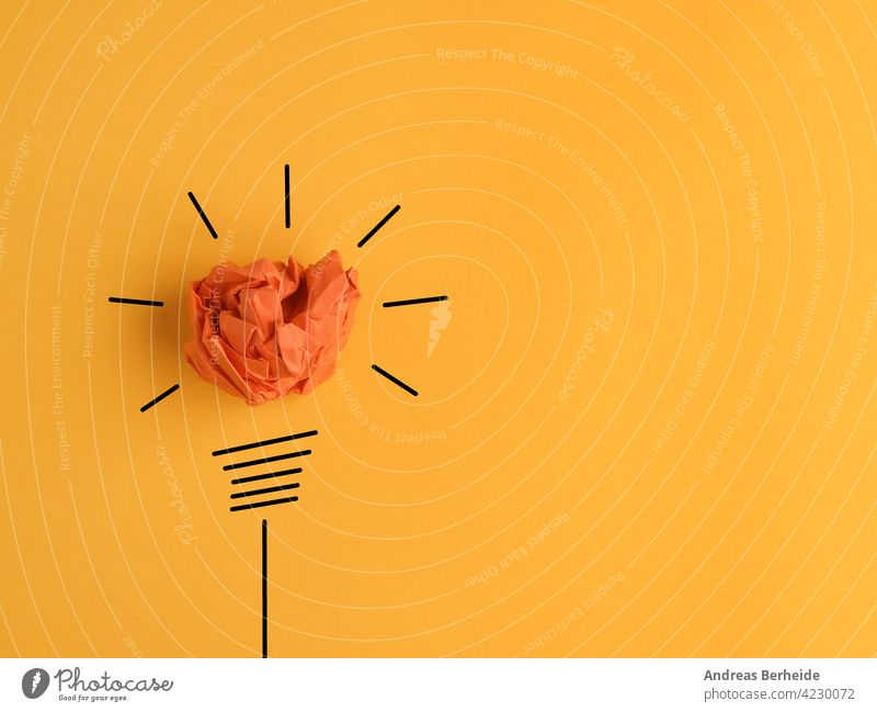 Crumpled paper ball as a lightbulb, conceptual business image for new ideas or creativity lamp energy drawing inspiration innovation power electricity bright