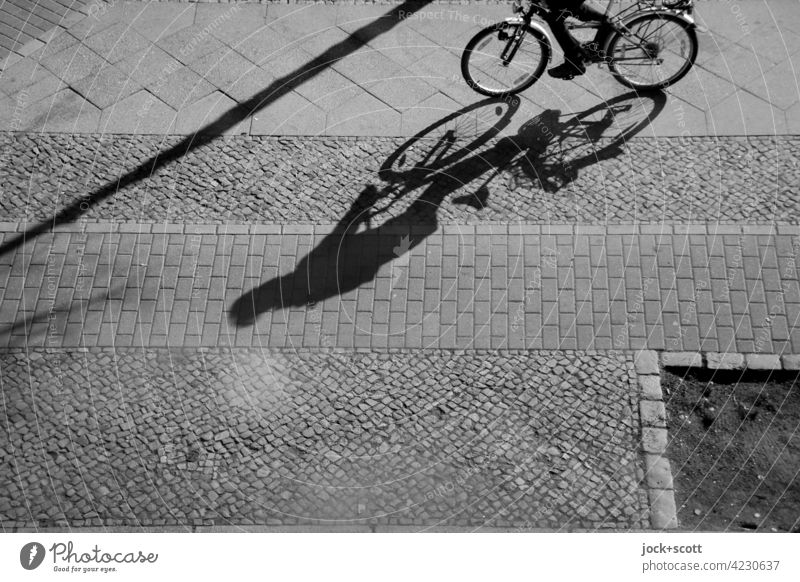 Cycling on the pavement Sidewalk Drop shadow Sunlight Silhouette Shadow play Structures and shapes Lanes & trails Paving stone Paving tiles Cycle path Bicycle
