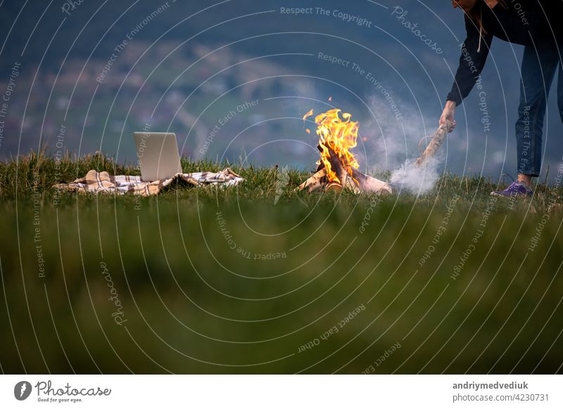 young woman freelancer throws firewood into a fire in the mountains in the evening. tourist girl resting and working outdoor female laptop sitting outside