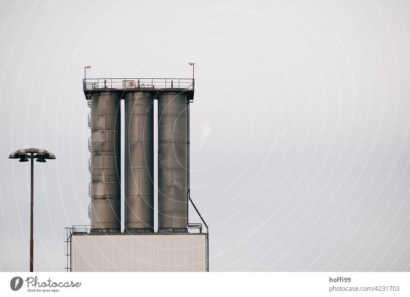 three silos in the harbour with spiral staircase and street lighting Silo Harbour Depot Logistics Minimalistic Industrial plant Storage Architecture Warehouse