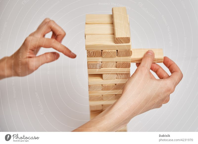 Family play board game. Hands take wooden block from tower. risk brick stack danger concept competition choice build object architecture development structure