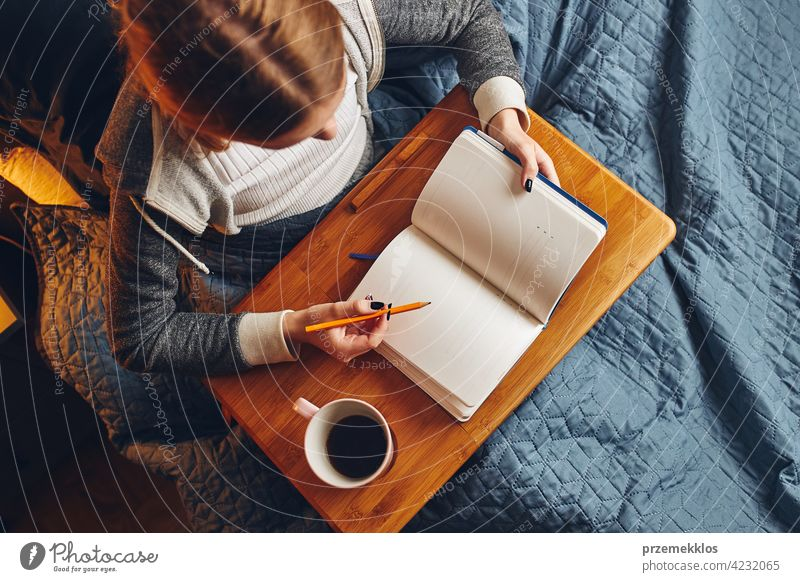Student learning at home. Young woman making notes, reading and learning from notepad. Girl writing journal sitting in bed education indoor student working
