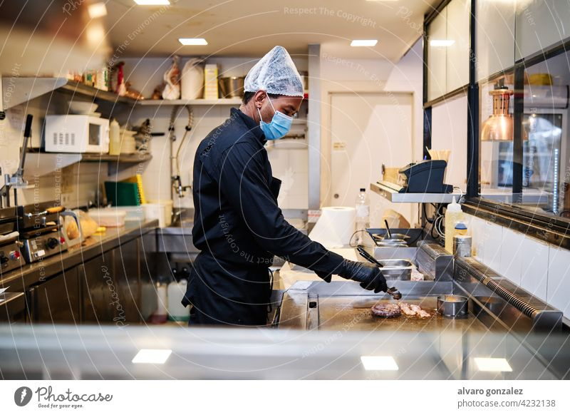 Close-up of professional latin chef man wearing a protective mask and uniform while working at restaurant kitchen. chief cooker worker staff stove indoors