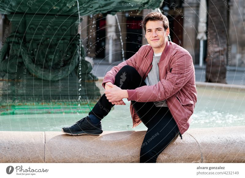Young man sitting in a water fountain outdoors. portrait young urban city street casual style smile alone jacket clothes caucasian travel tourist outside