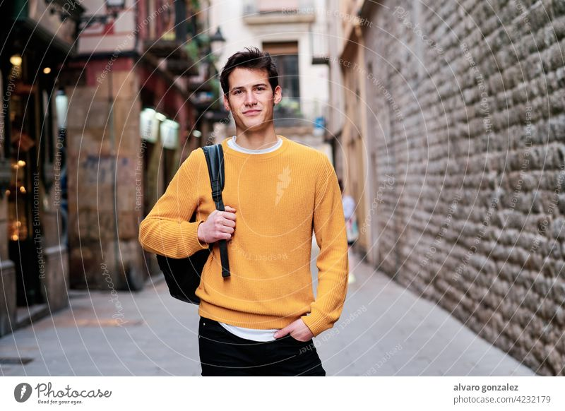 Portrait of young man standing outdoors on the street. portrait urban city confidence backpack posing stylish holding student looking outside confident style