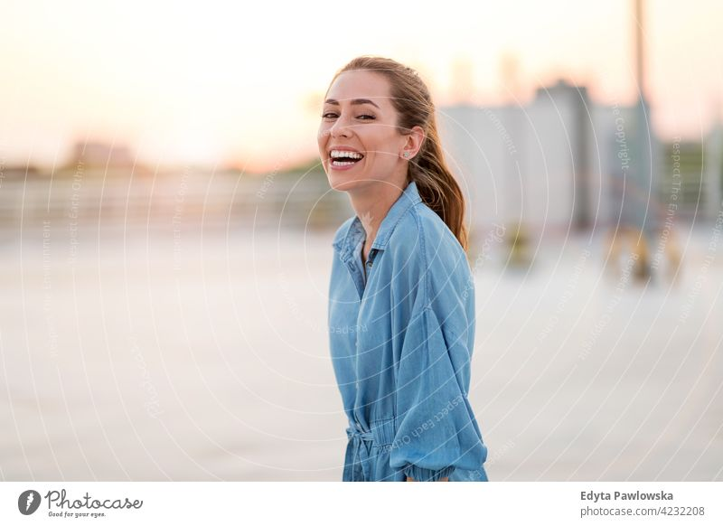 Portrait of an young woman on a rooftop enjoying sunset confident smiling female attractive beautiful young adult positive content standing lifestyle happy