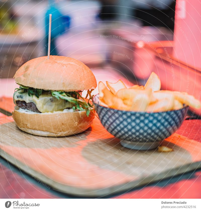 Gourmet burger with cheddar cheese and bacon accompanied by deluxe fries on a wooden board ketchup isolated Beef table Cholesterol mayonnaise sauce arugula