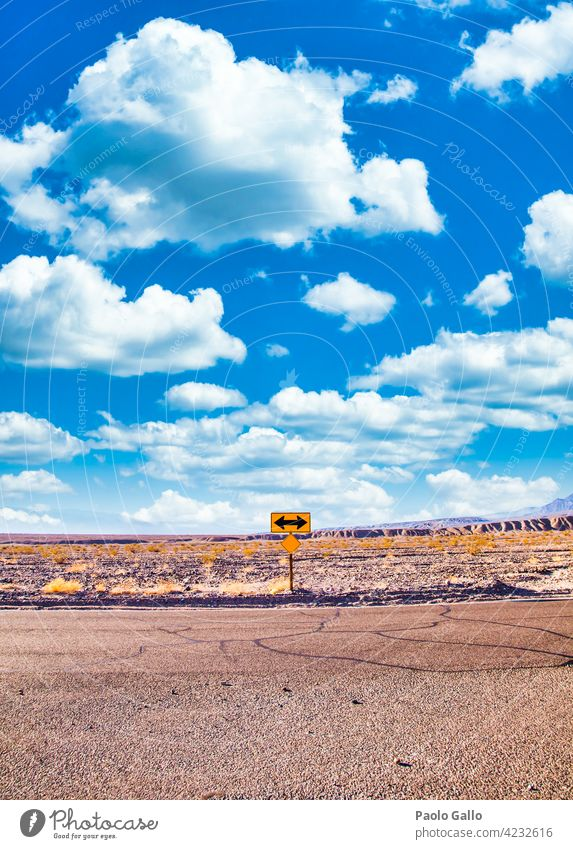 Directional sign in the desert with scenic blue sky and wide horizon. Concept for trip, freedom and transportation. Adventure Blue Cloud Desert Empty Freedom