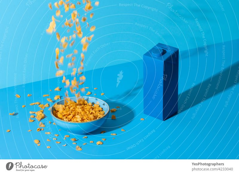 Pouring cornflakes cereal in a bowl on a blue table. Breakfast table in natural light. Abstract Accident background Blue Bottle Bowl Box Bright Carton Cereals