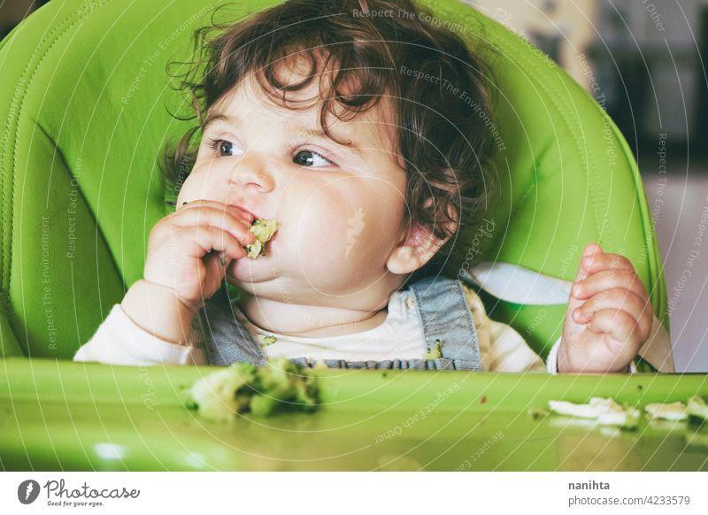 Baby eating food in her green highchair blw baby lead weading vegetables brocoli vegan vegetarian health healthy diet white caucasian complementary feeding