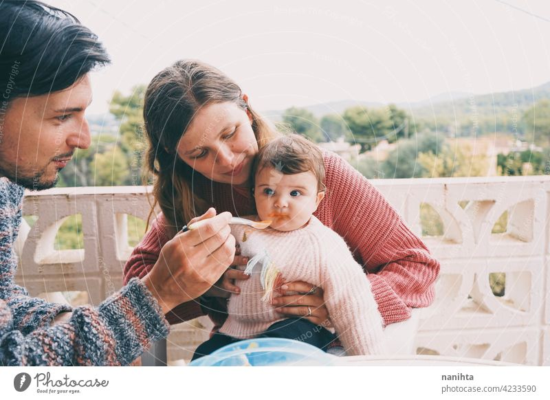 Real family sharing the first food of their baby real eating together complementary feeding mom dad childcare puree cream outdoors babyhood parenthood