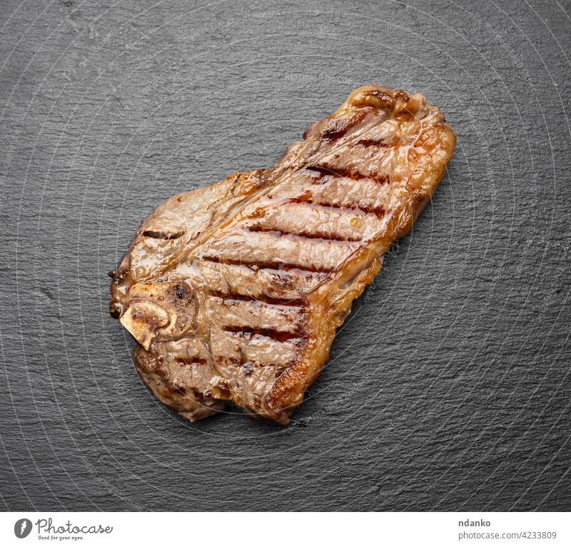 whole fried New York beef steak on a black board,  striploin doneness rare above barbecue bbq bloody brown cooked cut dinner fat fillet food grill grilled juicy