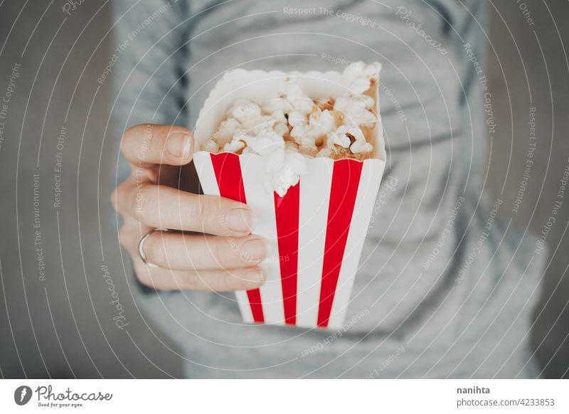 Woman holding a container full of pop corn cinema film vintage retro classic classy red white temptation snack woman enjoy hand lifestyle people food delicious