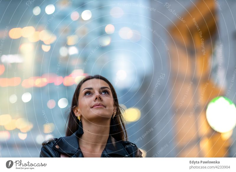 Portrait of young woman in the city at night urban street active people young adult casual attractive female happy Caucasian enjoying one person beautiful
