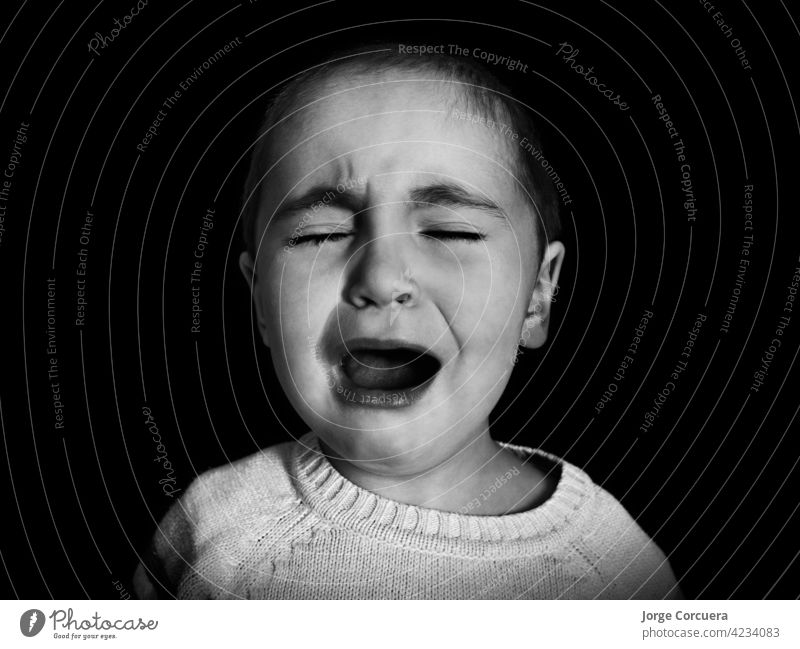 one year old girl with short hair cries uncontrollably in monochrome. Concept of anxiety, depression, childhood problems, emotions. cry sad baby young caucasian
