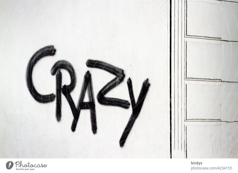 Crazy , black graffiti on white house wall crazy Characters Graffiti English unusual loopy differently universally evaluative descriptive Youth culture Word