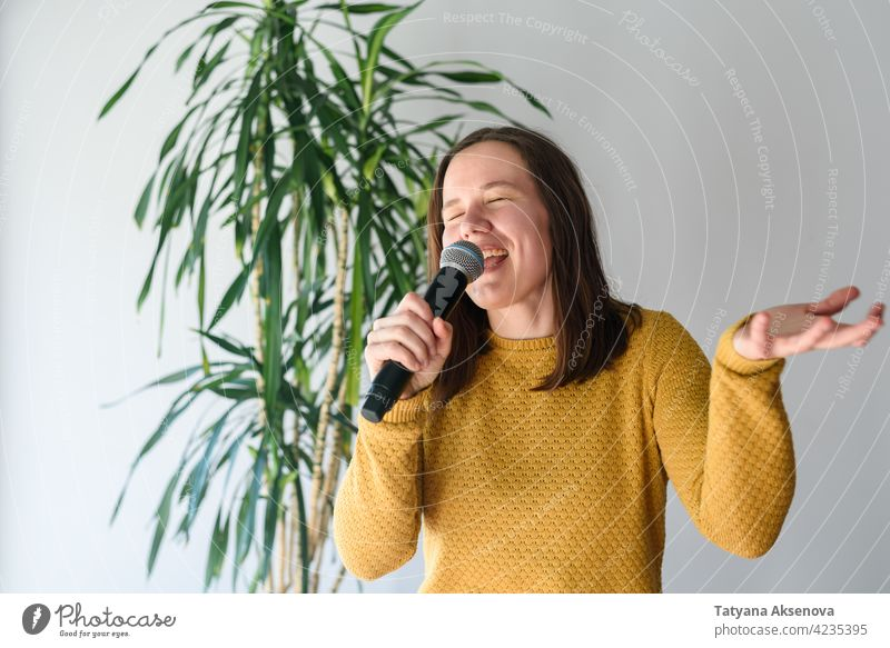 Woman singing with microphone woman fun karaoke song lifestyle performance expression person female music singer portrait sound stage happy caucasian audio