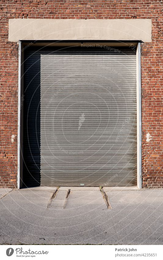 Rolling door in an old industrial hall made of bachstein. Goal Garage door Facade lorry Brick Deserted Building Closed Industrial hall Warehouse