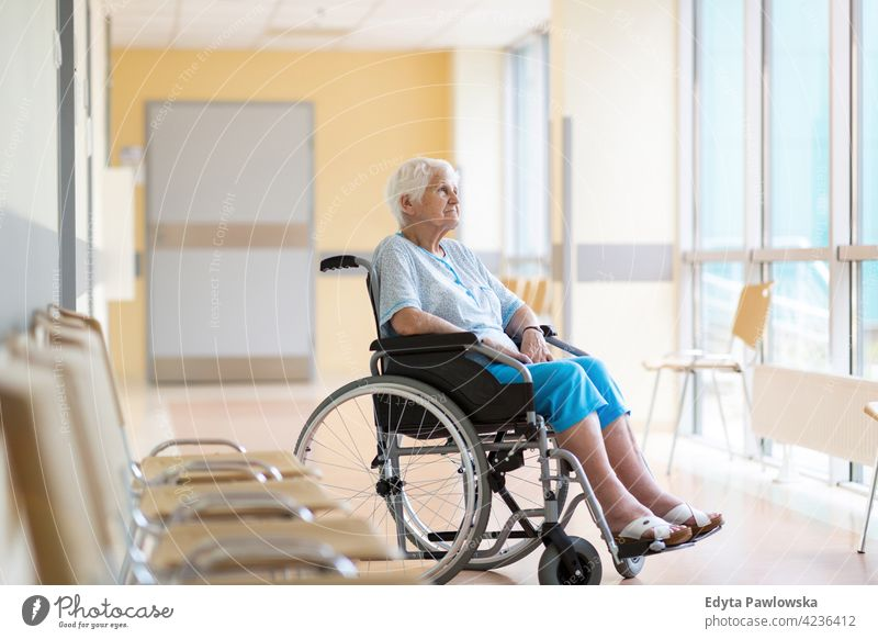 Senior woman sitting in wheelchair in hospital one person loneliness lonely alone wheel chair disability physical impairment Handicapped mobility support