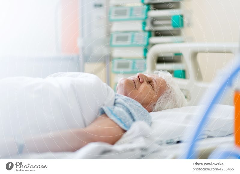 Senior female patient in hospital bed healthcare medicine indoors equipment clinic recovery help medical ward therapy working job occupation service confident