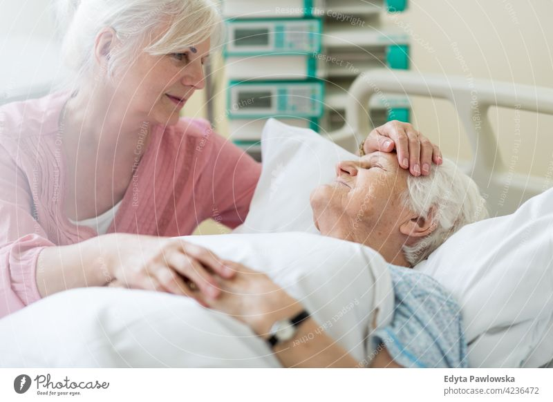 Daughter visiting her senior mother in hospital family daughter love together relationship kindness two people assistance trust gratitude help helping support