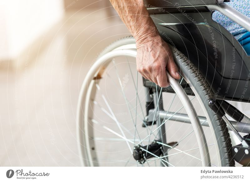 Senior person sitting in wheelchair unrecognizable person close-up hand one person loneliness lonely alone wheel chair disability physical impairment
