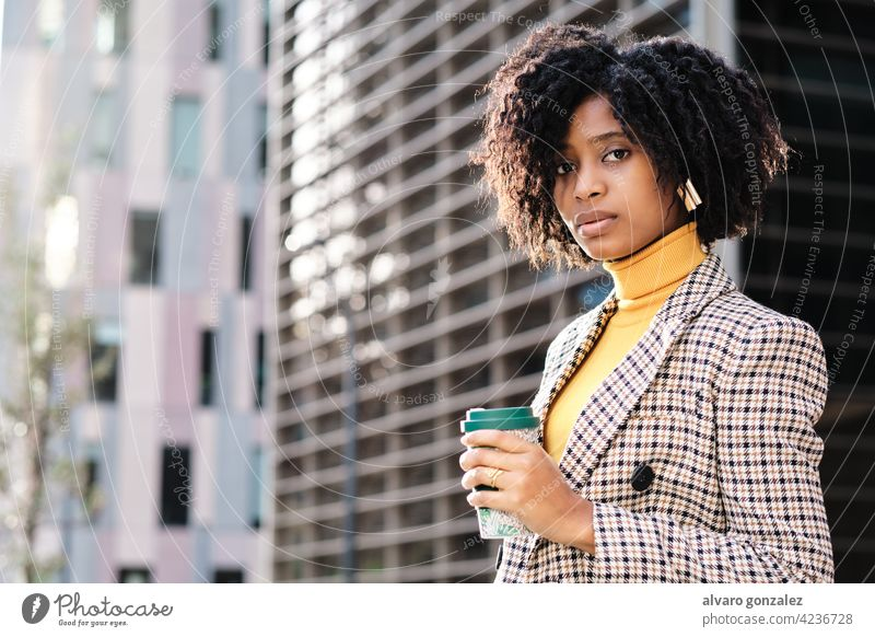 Business woman holding a cup of coffee outdoors. businesswoman afro urban city financial district street entrepreneur portrait professional confident work