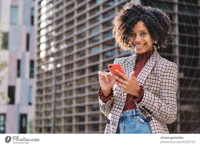 Business woman sending messages on her phone. business afro mobile financial district city urban outdoors professional street connection african american