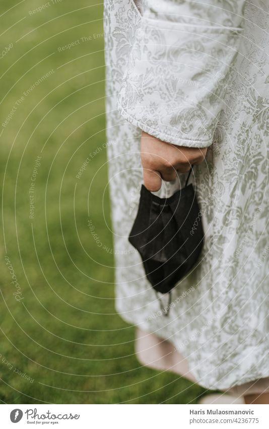 holding face mask in hand close up outdoors in nature 2019-ncov care closeup cloth corona virus coronavirus covid 19 covid-19 disease doctor dress epidemic