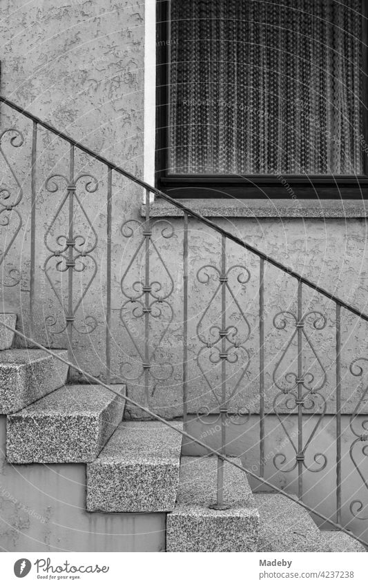 Bourgeois idyll with wrought iron banister and curtains behind the window of a residential house in Oerlinghausen near Bielefeld in the Teutoburg Forest in East Westphalia-Lippe, photographed in classic black and white