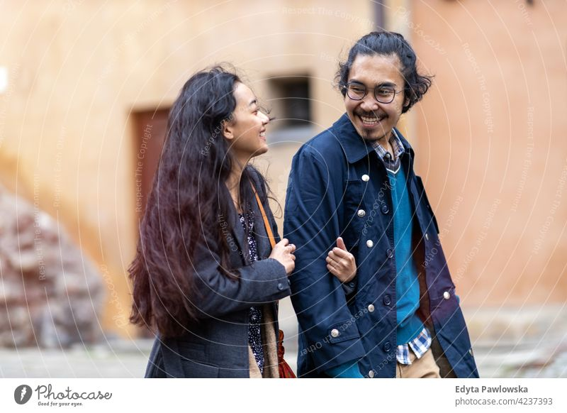 Happy young couple, walking through the old city, Warsaw, Poland warm clothing autumn fall urban Old Town people woman beautiful attractive girl male female