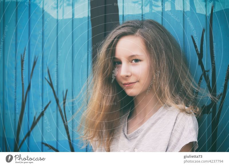 Portrait of smiling teenage girl with long hair, 13 years, in front of blue construction trailer Looking Human being 8 - 13 years Smiling Long-haired Girl