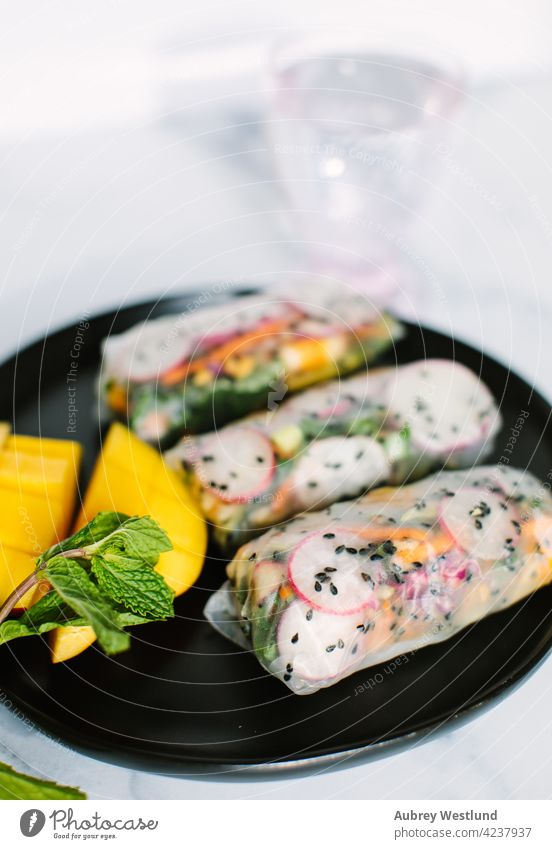 Colorful Viatnamese spring rolls with black sesame seeds, and mango on a black plate Asia Vietnam Vietnamese Vietnamese food appetizer asian avocado background