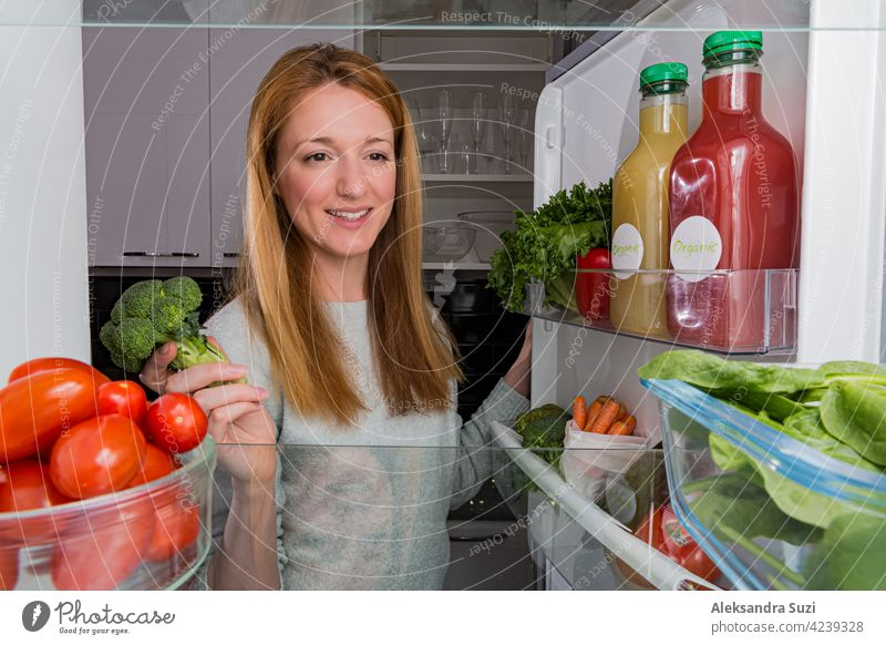 Open fridge from the inside, glass shelves with colourful vegetables, bottles of organic juices. Young woman with happy smile taking broccoli. Healthy eating, vegan concept.