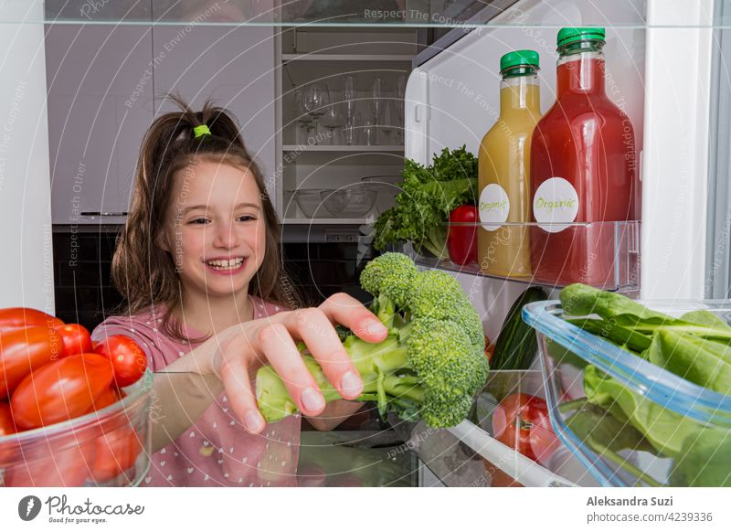 Open fridge from the inside, glass shelves with colourful vegetables, bottles of organic juices. Cute little girl with happy smile taking broccoli. Healthy eating, vegan concept.