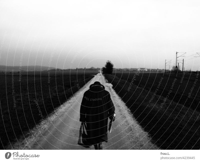 homecoming Woman Village off the beaten track Going Hat Coat Crooked Handbag fields Degersen Montage Loneliness Lonely sad Sadness Human being on one's own